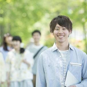 新緑の中で微笑む大学生の写真素材 [FYI04549003]