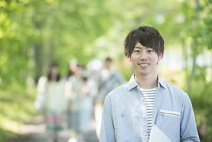 新緑の中で微笑む大学生の写真素材 [FYI04549005]