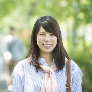 新緑の中で微笑む大学生の写真素材 [FYI04549008]