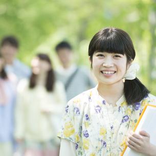 新緑の中で微笑む大学生の写真素材 [FYI04549011]