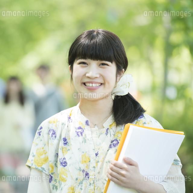 新緑の中で微笑む大学生の写真素材 [FYI04549013]