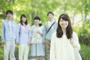 新緑の中で微笑む大学生の写真素材 [FYI04549018]