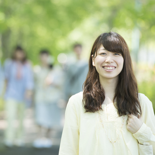 新緑の中で微笑む大学生の写真素材 [FYI04549019]