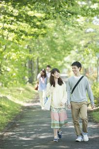 新緑の中を歩く大学生の写真素材 [FYI04549020]