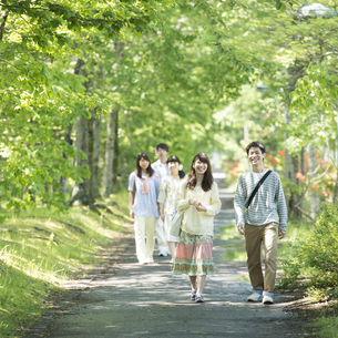 新緑の中を歩く大学生の写真素材 [FYI04549023]