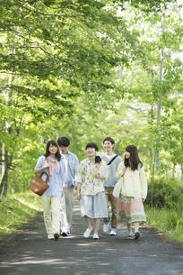 新緑の中を歩く大学生の写真素材 [FYI04549031]