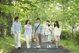 新緑の中を歩く大学生の写真素材 [FYI04549034]