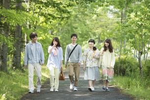 新緑の中を歩く大学生の写真素材 [FYI04549035]
