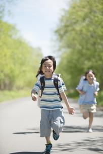 一本道を走る小学生の写真素材 [FYI04549075]