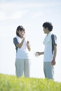 草原で水分補給をするカップルの写真素材 [FYI04549102]
