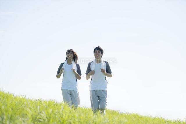 草原でジョギングをするカップルの写真素材 [FYI04549112]