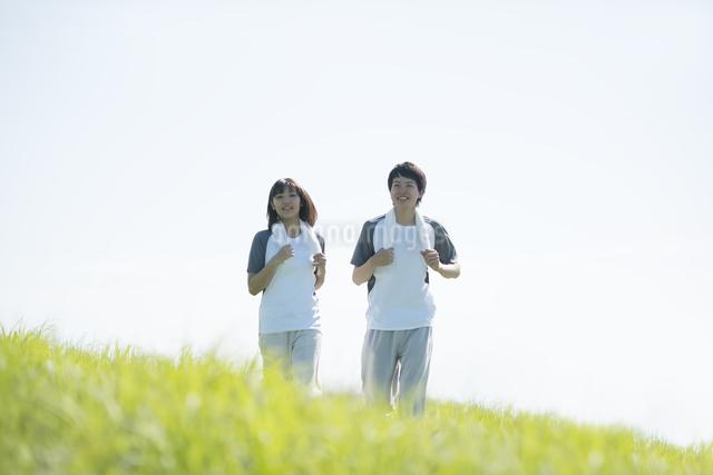 草原でジョギングをするカップルの写真素材 [FYI04549115]
