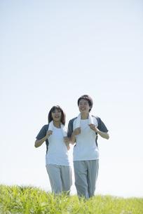 草原でジョギングをするカップルの写真素材 [FYI04549117]