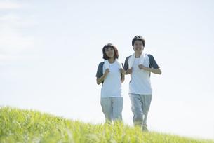 草原でジョギングをするカップルの写真素材 [FYI04549128]
