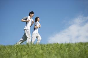 草原でジョギングをするカップルの写真素材 [FYI04549129]