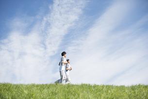 草原でジョギングをするカップルの写真素材 [FYI04549137]