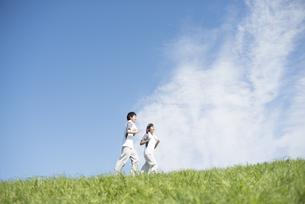 草原でジョギングをするカップルの写真素材 [FYI04549139]