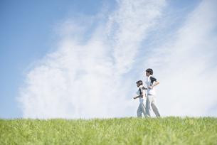草原でジョギングをするカップルの写真素材 [FYI04549141]