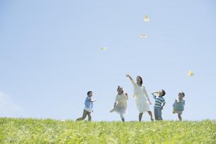 草原で紙飛行機を飛ばす小学生と先生の写真素材 [FYI04549161]