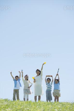 草原で楽器を持ち微笑む小学生の写真素材 [FYI04549165]