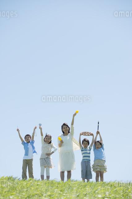 草原で楽器を持ち微笑む小学生の写真素材 [FYI04549166]