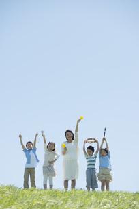 草原で楽器を持ち微笑む小学生と先生の写真素材 [FYI04549167]
