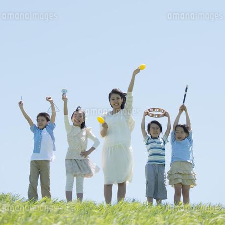 草原で楽器を持ち微笑む小学生の写真素材 [FYI04549168]
