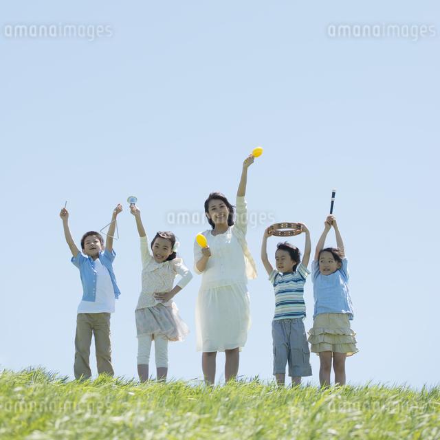 草原で楽器を持ち微笑む小学生と先生の写真素材 [FYI04549169]