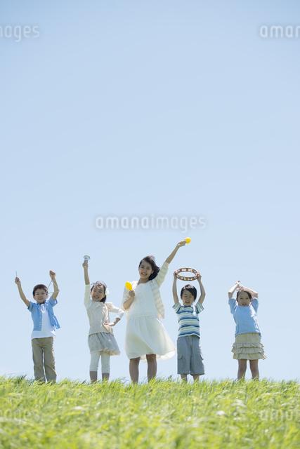 草原で楽器を持ち微笑む小学生と先生の写真素材 [FYI04549170]