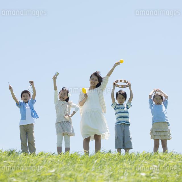 草原で楽器を持ち微笑む小学生と先生の写真素材 [FYI04549171]