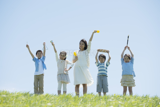 草原で楽器を持ち微笑む小学生と先生の写真素材 [FYI04549172]
