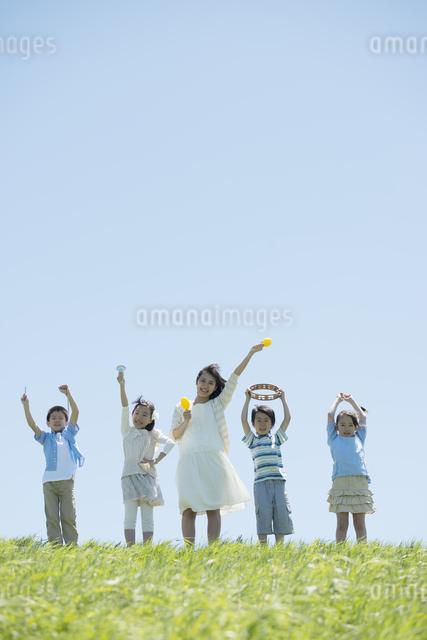 草原で楽器を持ち微笑む小学生と先生の写真素材 [FYI04549173]