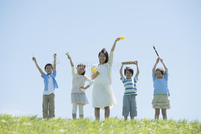 草原で楽器を持ち微笑む小学生と先生の写真素材 [FYI04549174]