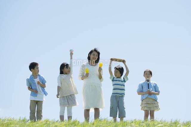 草原で楽器を持ち微笑む小学生と先生の写真素材 [FYI04549175]