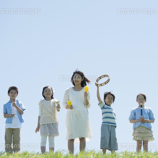 草原で楽器を持ち微笑む小学生と先生の写真素材 [FYI04549176]