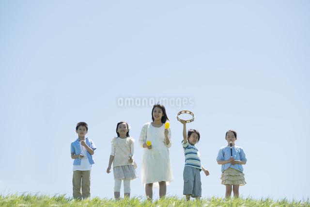 草原で楽器を持ち微笑む小学生と先生の写真素材 [FYI04549177]