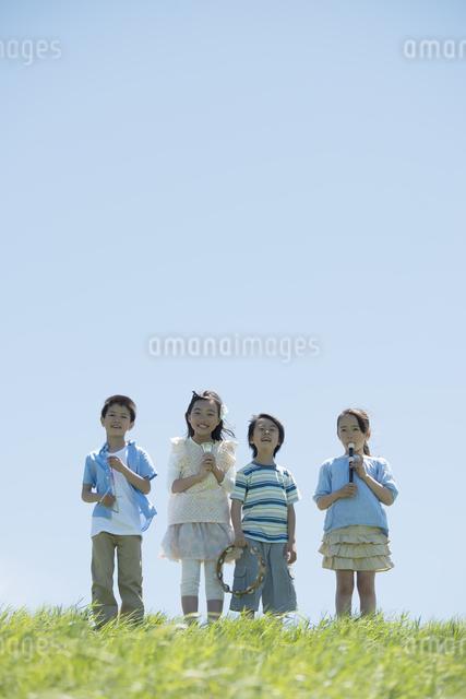 草原で楽器を持ち微笑む小学生の写真素材 [FYI04549178]