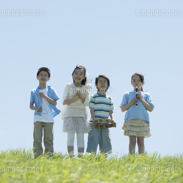 草原で楽器を持ち微笑む小学生の写真素材 [FYI04549179]