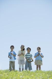 草原で楽器を持ち微笑む小学生の写真素材 [FYI04549180]