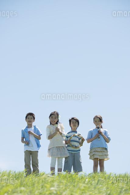 草原で楽器を持ち微笑む小学生の写真素材 [FYI04549181]