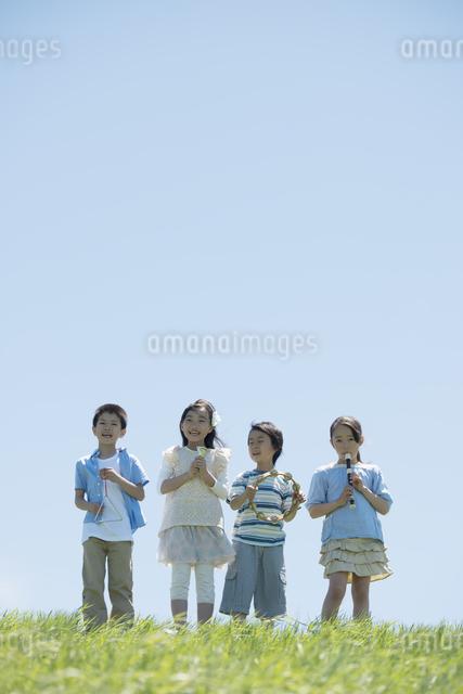 草原で楽器を持ち微笑む小学生の写真素材 [FYI04549182]