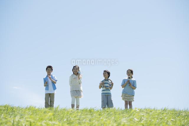 草原で楽器を持ち微笑む小学生の写真素材 [FYI04549183]