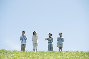 草原で楽器を持ち微笑む小学生の写真素材 [FYI04549184]