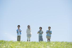 草原で楽器を持ち微笑む小学生の写真素材 [FYI04549185]
