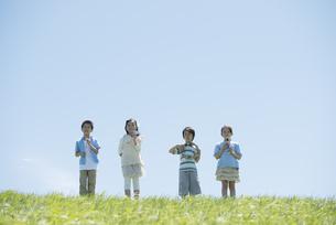 草原で楽器を持ち微笑む小学生の写真素材 [FYI04549186]