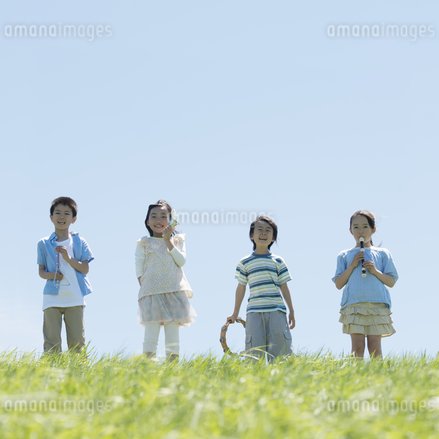 草原で楽器を持ち微笑む小学生の写真素材 [FYI04549187]