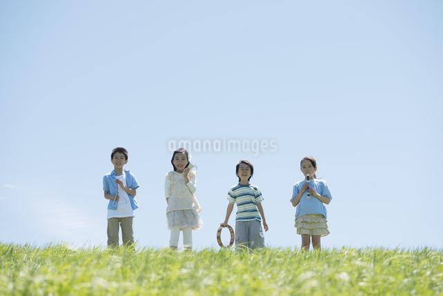草原で楽器を持ち微笑む小学生の写真素材 [FYI04549188]