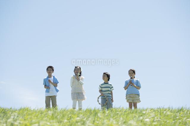 草原で楽器を持ち微笑む小学生の写真素材 [FYI04549189]