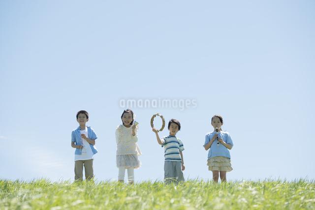 草原で楽器を持ち微笑む小学生の写真素材 [FYI04549190]