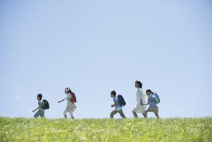 草原を歩く小学生と先生の写真素材 [FYI04549215]